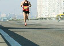 Ход марафона в свете утра Молодой человек бежать на мосте города Бег на дороге города Ноги бегуна спортсмена Город Blured стоковые фотографии rf