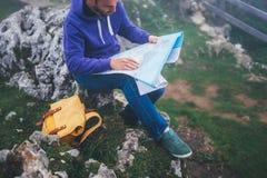 Молодой человек битника при рюкзак держа в руках и смотря на карте Испании туманной горы, туристского hiker путешественника на пр Стоковые Изображения RF