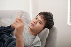 Молодой человек болен с гриппом, лежит дома под одеялом, принимает пилюльку стоковые изображения