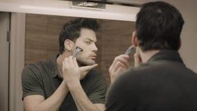 Молодой человек брея сторону перед зеркалом на bathroom Портрет красивого парня видеоматериал