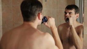 Молодой человек брея с электробритвой в ванной комнате парень бреет его бороду с бритвой в ванной комнате смотря внутри сток-видео