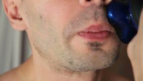 Молодой человек брея с электробритвой в ванной комнате closeup парень бреет его бороду с бритвой в ванной комнате видеоматериал