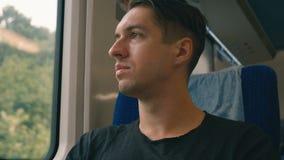 Молодой человек брюнета ехать в поезде Он смотрит внимательно вне окно сток-видео