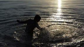 Молодой человек бьет воду озера для того чтобы развлечь на заходе солнца в slo-mo акции видеоматериалы