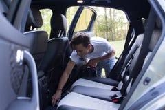 Молодой человек вакуумирует причудливый новый автомобиль стоковые фотографии rf