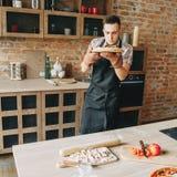Молодой человек варя домодельную пиццу стоковая фотография rf