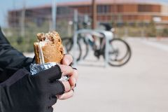 Молодой человек велосипедиста есть сандвич Стоковые Фотографии RF