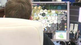 Молодой человек взгляда задней стороны сидит на компьютере и играет видеоигру акции видеоматериалы