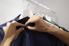 Молодой человек вися или unhanging рубашку Стоковые Фото