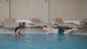 Молодой человек вползает вдоль края бассейна женщина смеется с ним акции видеоматериалы