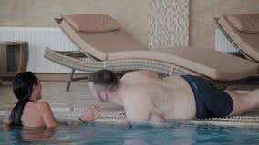 Молодой человек вползает вдоль края бассейна женщина смеется с ним видеоматериал