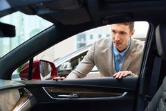 Молодой человек выбирая автомобиль для ренты стоковые фотографии rf