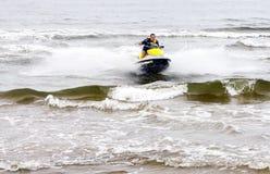 Молодой человек выполняя фокусы на лыже двигателя на море развевает стоковое изображение