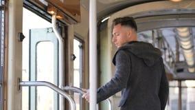 Молодой человек выходя на трамвай или старый автобус в городе акции видеоматериалы