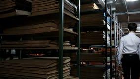 Молодой человек в белой рубашке бродяжничает между полками книг и взглядами вокруг Устанавливать старые библиотеку или архив  акции видеоматериалы