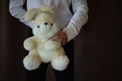 Молодой человек в белой рубашке и черных брюках держа зайца игрушки Человек с большим кроликом игрушки человек в любов подарок дл стоковые фотографии rf