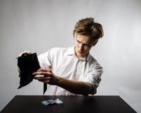 Молодой человек в белом и пустом бумажнике стоковое фото