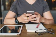 Молодой человек в вскользь используя smartphone, цифровую таблетку и noteboo стоковые фотографии rf