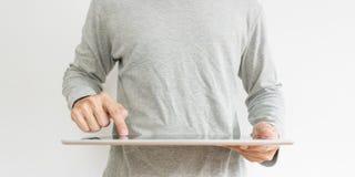 Молодой человек в вскользь серой ткани, работая на цифровой таблетке на белой предпосылке Стоковые Изображения RF