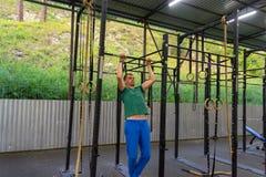Молодой человек в голубых брюках спорт и зеленой футболке выполняет бывшее стоковые изображения rf
