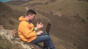 Молодой человек в желтой куртке, голубых джинсах и стеклах сидит в горах, работы для ноутбука, нервны, клянутся сток-видео