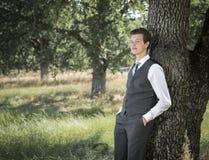 Молодой человек в костюме и связь outdoors полагаясь против дерева стоковое изображение rf