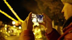 Молодой человек в красной куртке делает фото со смартфоном в вечере на предпосылке освещения рождества Съемка на красном стоковые фото