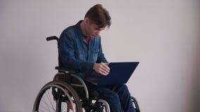 Молодой человек в кресло-коляске используя современный ноутбук и сидеть дома видеоматериал
