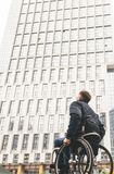 Молодой человек в кресло-коляске против фона современного многоэтажного здания стоковые фото