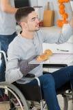 Молодой человек в кресло-коляске раскрывает печь для того чтобы подготовить еду Стоковое Фото