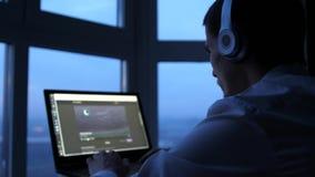 Молодой человек в наушниках использует фильм дозора планшета панорамным окном в вечере 3840x2160, 4K сток-видео