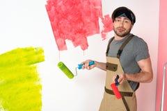 молодой человек в работе общих роликов краски удерживания и делать жест пожимания плечами перед покрашенный стоковые фотографии rf