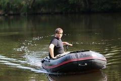 Молодой человек в раздувной шлюпке с рыбной ловлей на реке Стоковое Изображение RF