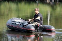 Молодой человек в раздувной шлюпке с рыбной ловлей на реке Стоковая Фотография RF