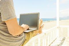 Молодой человек в серой рубашке сидя на пляже, работая на компьтер-книжке Блоггер, писатель, кодер, researchin просматривать удал стоковое фото