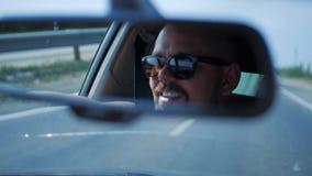 Молодой человек в солнечных очках управляет автомобилем Сторона отражения в зеркале заднего вида корабля акции видеоматериалы