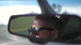 Молодой человек в солнечных очках управляет автомобилем Сторона отражения в зеркале заднего вида корабля видеоматериал