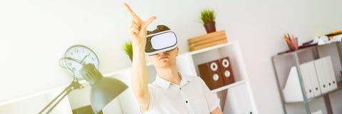 Молодой человек в стеклах виртуальной реальности стоит около таблицы и вытягивает его руку вверх Молодой человек thumbs виртуальн стоковое фото