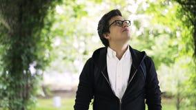 Молодой человек в стеклах наслаждаясь прогулкой в парке видеоматериал