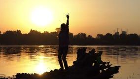 Молодой человек в танцах наушников, поднимает руки на заходе солнца в slo-mo сток-видео