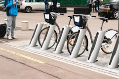 Молодой человек в телефоне и чемодане стоит около парка велосипеда Велосипед для ренты Стоковое Изображение