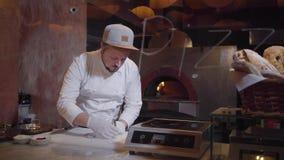 Молодой человек в форме шеф-повара подготавливая сырые рыбы на разделочной доске Повар принимает вне косточки от филе используя с сток-видео