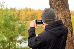 Молодой человек в черной куртке и связанной серым цветом шляпе принимает фото ландшафта осени на мобильном телефоне в лесе Стоковые Фотографии RF