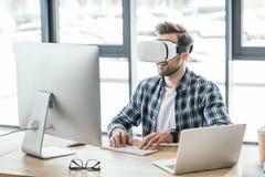 молодой человек в шлемофоне виртуальной реальности используя настольный компьютер и ноутбук на рабочем месте стоковая фотография