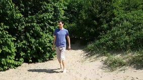Молодой человек в шортах и футболках на песке Человек хромает, он имеет инвалидность - церебральный паралич сток-видео