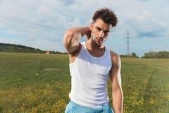 Молодой человек в undershirt аранжирует его волосы снаружи стоковое изображение rf
