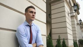 Молодой человек говорит на телефоне стоя на улице видеоматериал