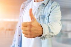 Молодой человек давая большой палец руки вверх на офисе Стоковые Фотографии RF