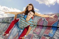 Молодой человек давая piggyback к смеясь над женщине стоковые изображения rf