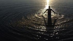 Молодой человек делает брызгает воду озера повышения на заходе солнца в slo-mo сток-видео